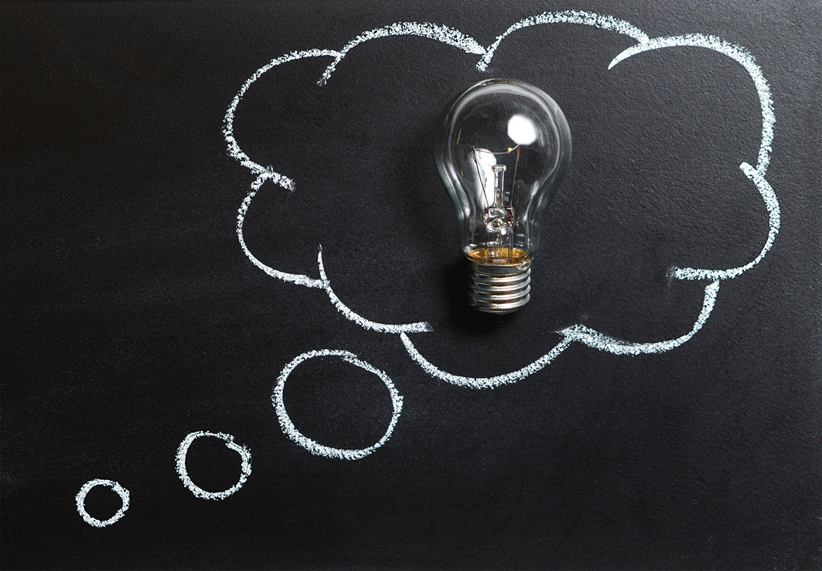 Speech bubble on chalkboard with a light bulb for FAQ pages